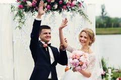 Hübscher glücklicher Bräutigam und schöne blonde Braut in weißem Kleid c Stockfotos