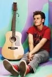 Hübscher glücklicher Junge spielt auf Akustikgitarre auf einem farbigen Ba Lizenzfreies Stockbild