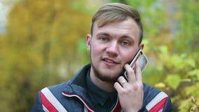 Hübscher glücklicher junger Mann spricht durch den Handy, der nahe gelben Büschen steht stock footage