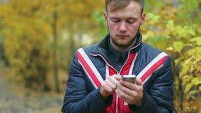Hübscher glücklicher junger Mann spricht durch den Handy, der nahe gelben Büschen steht stock video