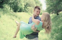 Hübscher glücklicher Mann, der an das Handlieblingsmädchen, Paar hält Lizenzfreies Stockfoto