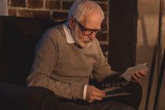 hübscher grauer Haarmann, der im Lehnsessel sitzt und alte Fotos betrachtet Lizenzfreie Stockfotos