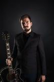 Hübscher grober Kerl mit Bart auf dunklem Hintergrund Stockfotografie
