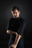 Hübscher grober Kerl mit Bart auf dunklem Hintergrund Lizenzfreie Stockfotografie
