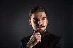 Hübscher grober Kerl mit Bart auf dunklem Hintergrund Stockbild