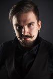 Hübscher grober Kerl mit Bart auf dunklem Hintergrund Lizenzfreies Stockbild