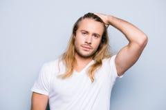Hübscher grober Mann mit Borste kämmt sein langes blondes Haar Stockfotografie