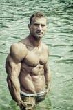 Hübscher, heißer junger Bodybuilder im Meer Stockfotos