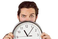 Hübscher Hippie, der eine Uhr zeigt Stockbild