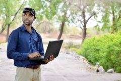 Hübscher Hippie-Geschäftsmann, der an Laptop arbeitet lizenzfreies stockbild