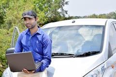 Hübscher Hippie-Geschäftsmann, der an Laptop mit Auto arbeitet stockbild