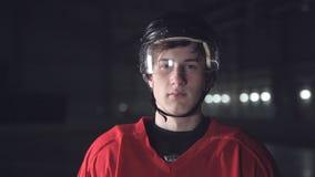 Hübscher Hockeyspieler An der Kamera auf der dunklen Arena lächeln, nah herauf Porträt des Verteidigers oder vorwärts des kanadis stock video