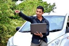Hübscher indischer Geschäftsmann, der an Laptop mit Auto arbeitet stockfotos