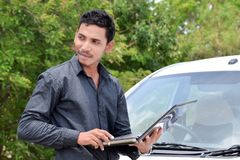 Hübscher indischer Geschäftsmann, der an Laptop mit Auto arbeitet stockbilder