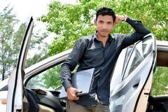 Hübscher indischer Geschäftsmann, der an Laptop mit Auto arbeitet lizenzfreies stockfoto