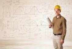 Hübscher Ingenieur, der mit Hand gezeichnetem Hintergrund berechnet Lizenzfreie Stockbilder
