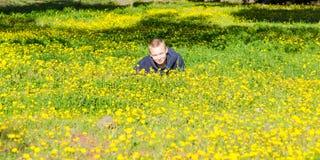 Hübscher Junge, der auf das blühende Feld des Frühlinges legt Stockbilder