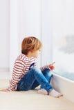 Hübscher Junge, der auf Teppich nahe dem Fenster am regnerischen Tag sitzt Stockfoto