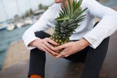 Hübscher Junge, der draußen mit Ananas auf dem Naturhintergrund sitzt Stockfoto