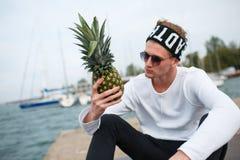 Hübscher Junge, der draußen mit Ananas auf dem Naturhintergrund sitzt Lizenzfreie Stockfotos