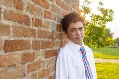 Hübscher Junge, der an einer Backsteinmauer bei Sonnenuntergang sich lehnt Stockfotos