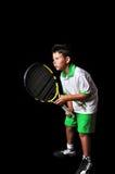 Hübscher Junge, der mit der Tennisausrüstung erwartet Aufschlag aufwirft Stockbilder