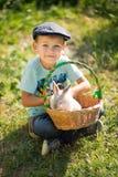 Hübscher Junge des netten Landwirts in den Jeans Sommertag im Dorfleben mit Blumen genießend happyly lächelnd mit Kaninchenhäsche Lizenzfreies Stockbild
