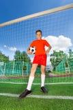 Hübscher Junge mit Fußball steht nahe Holzarbeit Stockfotos