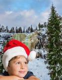 Hübscher Junge in rotem Santa Claus-Hut lizenzfreie stockfotografie