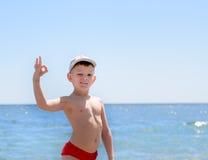 Hübscher Junge am Strand, der okayhandzeichen zeigt Lizenzfreies Stockbild