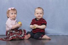 Hübscher Junge und Mädchen auf dem blauen Hintergrund Äpfel essend Stockfotos