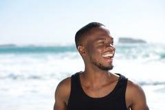 Hübscher junger Afroamerikanermann, der über den Strand lacht Lizenzfreies Stockbild