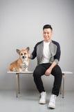 Hübscher junger asiatischer Mann, der mit seinem Hund auf Stuhl sitzt stockbild