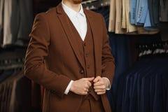 Hübscher junger bärtiger Geschäftsmann in der klassischen Klage Mann trägt eine Jacke Es ist im Ausstellungsraum und versucht auf Stockfoto