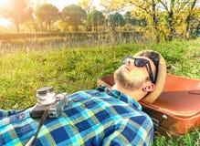 Hübscher junger bärtiger Hippie, der mit alter Kamera sich entspannt Lizenzfreies Stockfoto