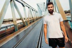 Hübscher junger bärtiger Mann, der über Brücke läuft Lizenzfreie Stockfotos