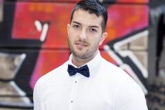Hübscher junger bärtiger Mann mit weißem Hemd und Fliege auf der Straße Lizenzfreies Stockfoto