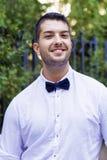 Hübscher junger bärtiger Mann mit weißem Hemd und Fliege auf der Straße Stockfotografie