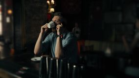 Hübscher junger bärtiger Mann steht und spricht über das Telefon und das trinkende cofee am Café stock video footage
