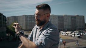 Hübscher junger bärtiger Mann steht und spricht am Telefon und betrachtet die Uhr auf die Stadt stock footage
