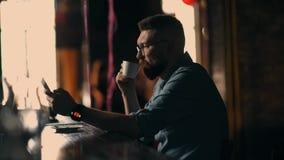 Hübscher junger bärtiger Mann untersucht das Telefon und Getränk cofee im Café stock footage
