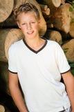 Hübscher junger blonder Junge, der nahe einem hölzernen Stapel aufwirft Stockfotografie