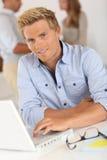 Hübscher junger blonder Mann, der im Büro sitzt Stockfotografie
