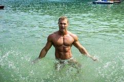 Hübscher junger Bodybuilder im Meer, Spritzwasser oben Lizenzfreies Stockfoto