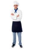 Hübscher junger Chef, der in der Uniform aufwirft stockbild