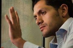 Hübscher junger deprimierter Mann, der durch das Fenster, grauer Hintergrund aufpasst Stockfotografie