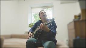 Hübscher junger die Gitarre spielender und singender Musiker Mann, der Akustikgitarre-Abschluss herauf Zeitlupevideolebensstil sp stock footage