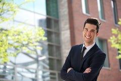 Hübscher junger Geschäftsmann, der draußen lächelt Stockfotografie