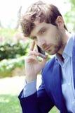 Hübscher junger Geschäftsmann, der einen Anruf mit seinem Smartphone draußen in einem grünen Park macht lizenzfreie stockfotografie