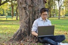 Hübscher junger Geschäftsmann, der einen Baum lehnt und Laptop mit seiner Arbeit am Sommerpark verwendet Stockfoto